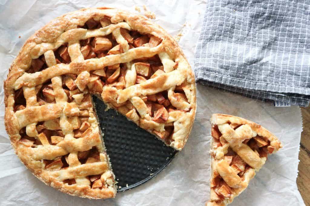 Dutch apple pie cut with a piece beside it.