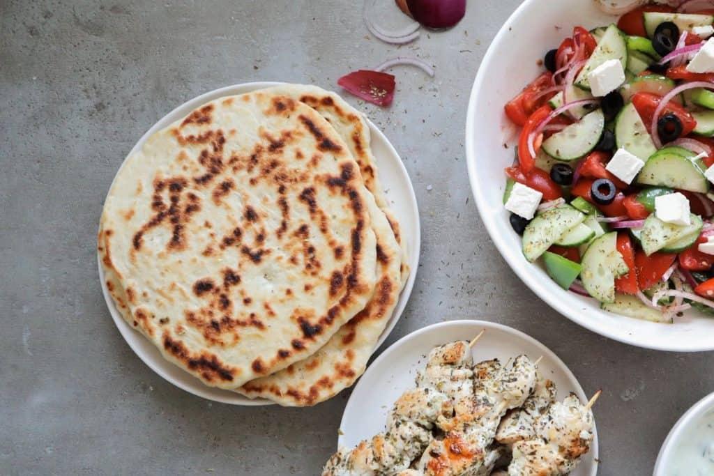 Greek pita bread with a salad and souvlaki on a grey background