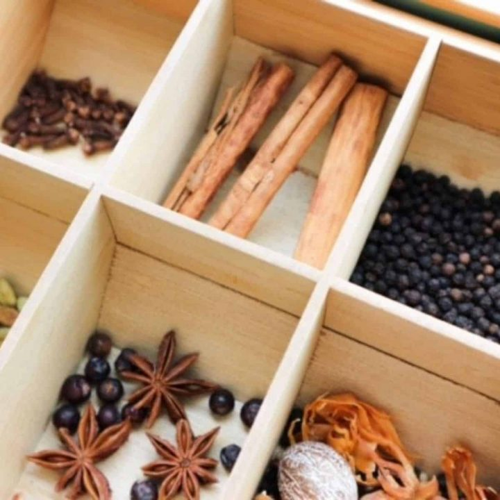 Unground spices for speculaas spice mix in a wooden box