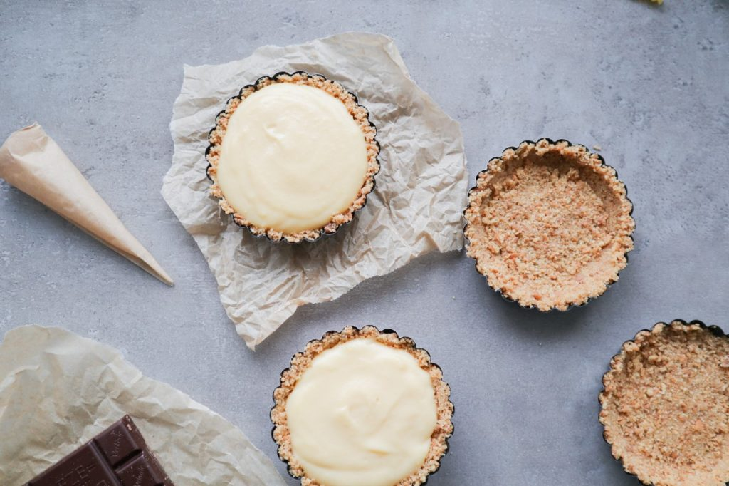 four little pie crusts while filling them with vanilla cream and decorating them with chocolate